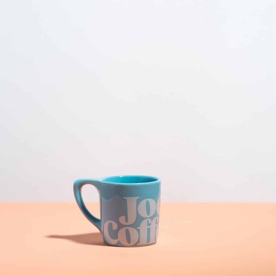 "blue mug with ""joe coffee"" on it"