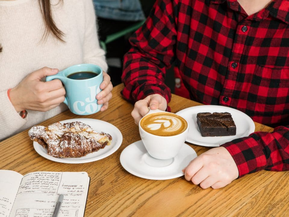 couple drinking coffee, eating baked goods